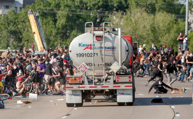 V Minneapolisu, kjer je Floyd tragično umrl med aretacijo, je voznik tovornjaka cisterne zapeljal proti množici protestnikov, ki je korakala po eni od glavnih cest. Protestniki so se še pravočasno umaknili, nato pa voznika cisterne potegnili iz vozila in ga pretepli. S poškodbami je bil odpeljan v bolnišnico. Motiv dejanja še ni znan. FOTO: Eric Miller/Reuters