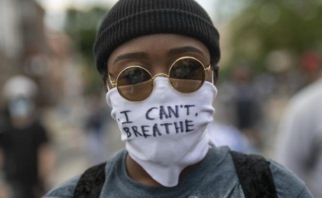 """Protestnik z masko, na kateri so zapisane zadnje besede Georgea Floyda """"Ne morem dihati!""""Foto Mark Makela Afp"""