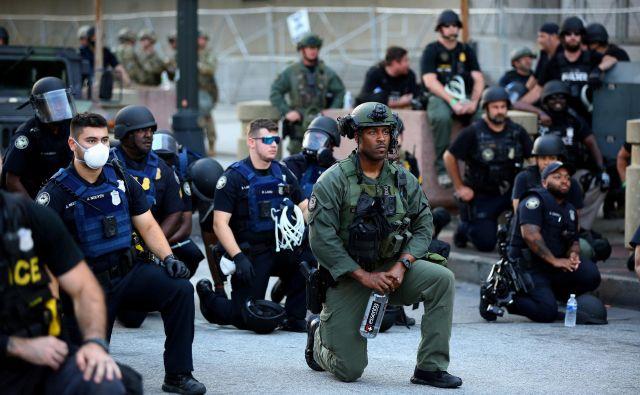 Med protesti v centru Atlante v ameriški zvezni državi Georgia so se tudi nekateri policisti skupaj s protestniki poklonili umrlemu temnopoltemu Georgeu Floydiu tako da so počepnili. FOTO: Dustin Chambers/Reuters