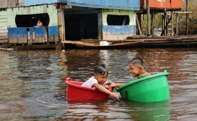 Otroci se igrajo v vedrih na reki Amazon v pristaniški skupnosti Belen v Peruju. »Peru se srečuje s pomanjkanjem kisika za zdravljenje bolnikov s koronavirusom, zato vlada načrtuje povečanje lokalne proizvodnje in uvoza, da bi zagotovila oskrbo kisika,« je poročal perujski minister za zdravje. Peru je za Brazilijo druga država v Latinski Ameriki po številu okužb s COVID-19 z več kot 4600 smrtnimi primeri. FOTO: Cesar Von Bancels/Afp