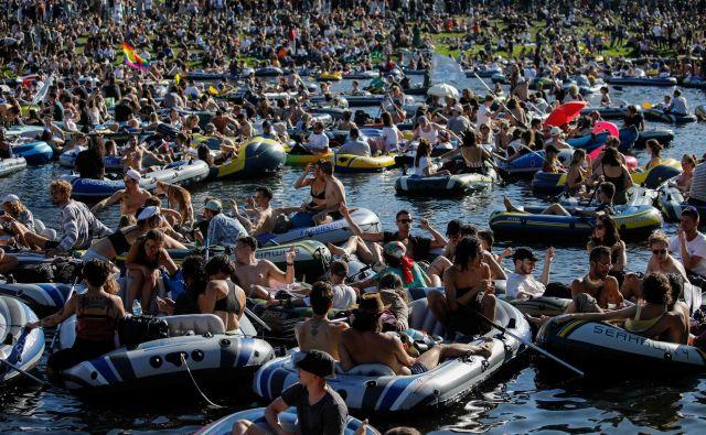 Na kanalu Landwehr v berlinskem okrožju Kreuzberg se je mladina v čolnih udeležila množičnega rejv partija, da bi podprli svetovno znane plesne klube v Berlinu, ki so na robu propada zaradi pandemije koronavirusa. FOTO: David Gannon/Afp
