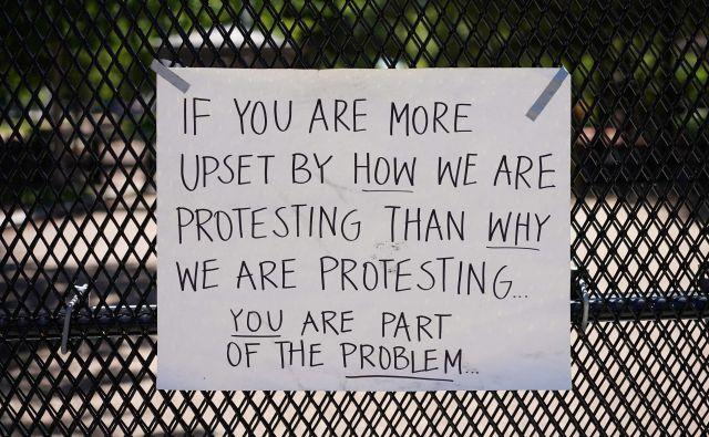Sporočilo, pritrjeno na varnostno ograjo na severni strani trga Lafayette blizu Bele hiše v Washingtonu. FOTO: Mandel Ngan/Afp
