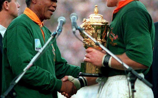 Poseben trenutek v zgodovini Južne Afrike predstavlja slovesna razglasitev svetovnih prvakov v ragbiju 1995, ko je Nelson Mandela predal pokal domačemu kapetanu Francoisu Pienaarju. FOTO: Reuters