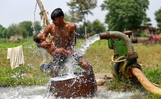 Moški hladi sina z vodo iz vodne cevi na polju na obrobju New Delhija na vroč poletni dan. FOTO: Money Sharma/Afp