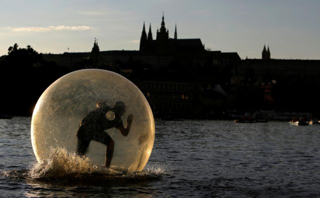 Moški se po Vltavi skozi Prago prevaža v plastičnem mehurčku, v mehurčku z le malo okužbami pa so koronakrizo za zdaj preživele države višegrajske četverice. Foto: Reuters