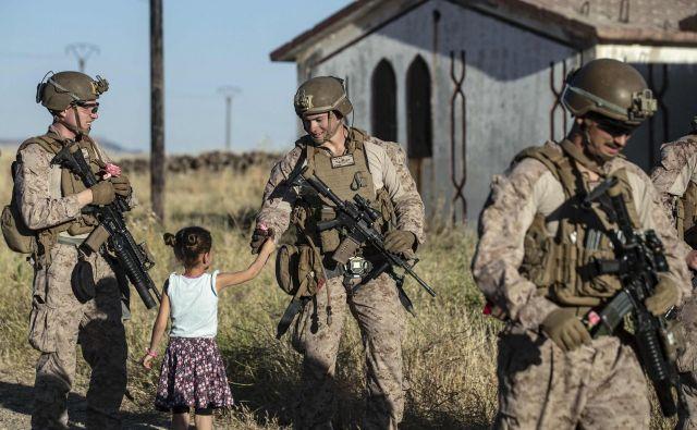 Sirska deklica ameriškim vojakom deli cvetje, medtem ko se je njihov konvoj ustavil na podeželju severovzhodnega sirskega mesta Al Malikiyah (Derik) ob meji s Turčijo. FOTO: Delil Souleiman/AFP