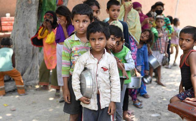 Indijski otroci iz revnega predela New Delhija čakajo v vrsti za brezplačno hrano. FOTO: Prakash Singh/Afp<br />