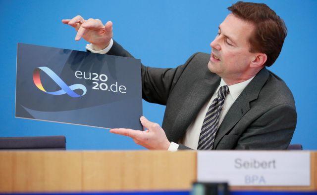 V času prihodnjega tria (Nemčija, Portugalska, Slovenija) bo predsedovanje svetu EU najprej prevzela Nemčija, ki se bo morala spopasti s številnimi omejitvami, povezanimi s pandemijo. Na fotografiji tiskovni predstavnik nemške vlade Steffen Seibert predstavlja logo nemškega predsedovanja. FOTO: Hannibal Hanschke/Reuters