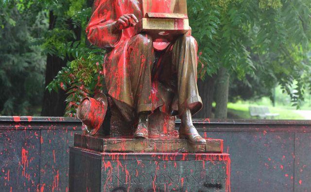 Kip so pobarvali na rdeče in zapisali 'rasist, posiljevalec'. Foto Miguel Medina/AFP
