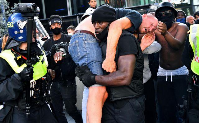 Na ulice britanske prestolnice so se podali nasprotniki rasizma in skrajno desne skupine. Med demonstracijami je protestnik pretepenega in poškodovanega udeleženca na rami odnesel proti varnostikom v bližini postaje Waterloo v Londonu. FOTO: Dylan Martinez/Reuters