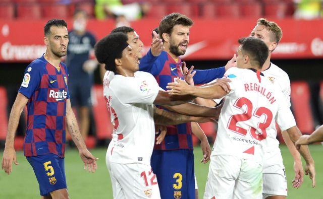 Gerard Pique (Barcelona) se je med tekmo takole jezil na Sergia Reguilona (Sevilla). FOTO: Cristina Quicler/AFP