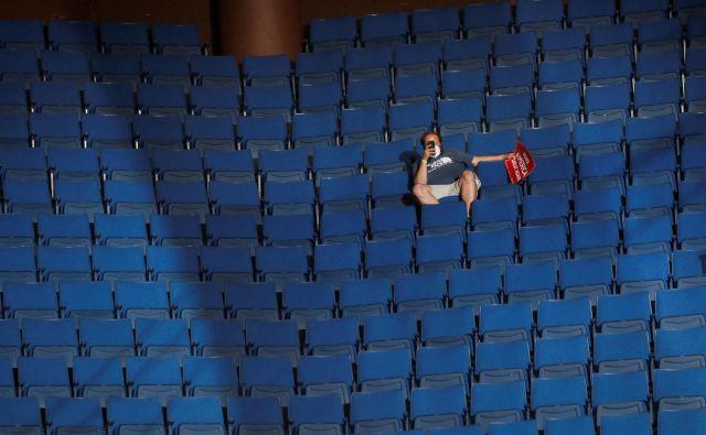 Osamljen Trumpov privrženec v zgodnjem delu arene v Tulsi. FOTO: Leah Millis/Reuters