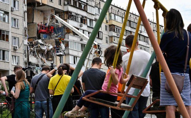Lokalni prebivalci Kijeva opazujejo reševalce, kako odstranjujejo ruševine v stanovanjskem naselju, kjer je prišlo do plinske eksplozije. Ena oseba je umrla, uničenih je več stanovanj. FOTO: Genya Savilov/Afp<br />