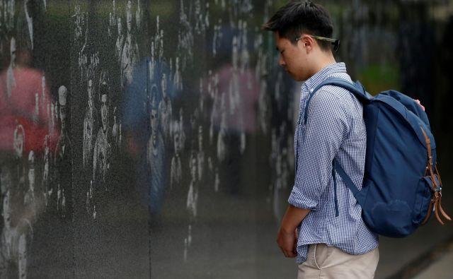 Kanadski južnokorejec Charles Choi stoji pred spomenikom veteranom korejske vojne v Washingtonu. Foto Leah Millis/Reuters