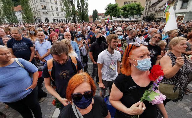 Veliko ljudi je na Prešernovem trgu nosilo cvetje. FOTO: Foto Jože Suhadolnik/Delo
