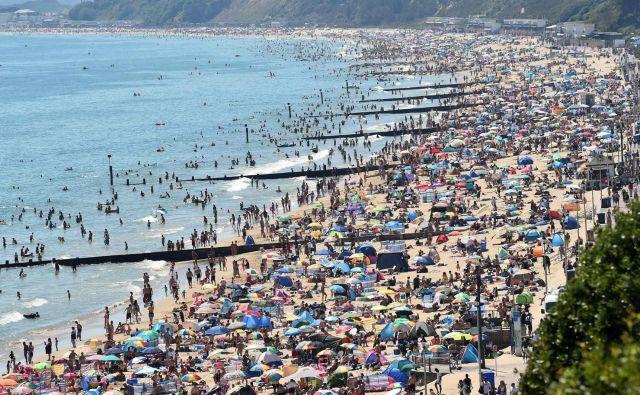 Prenatrpana plaža v Bournemouthu.<strong> </strong>Le nekaj dni po odpravi karantene in evropskih omejitev potovanja so mnogi Britanci ostali doma na hladnem, saj je toplotni val prizadel otok s temperaturami blizu 40 stopinj Celzija. Velika Britanija ni sposobna preprečiti poplave obiskovalcev svojih plaž zaradi visokih temperatur, ki naj bi trajale do konca tedna. FOTO: Glyn Kirk/Afp<br />