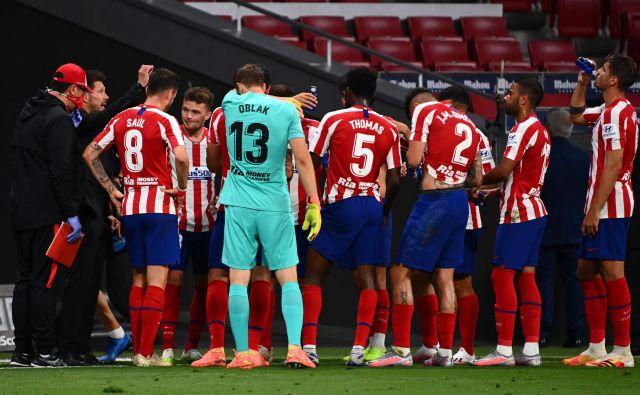 Diego Simeone (drugi z leve) se je z nogometaši Atletica, med njimi tudi našim Janom Oblakom, veselil nove zmage. FOTO: Gabriel Bouys/AFP