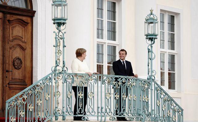 Francoski predsednik Emmanuel Macron in nemška kanclerka Angela Merkel sta na srečanju na gradu Meseberg upoštevala ukrepe zdravstvene stroke. FOTO: Kay Nietfeld/Reuters