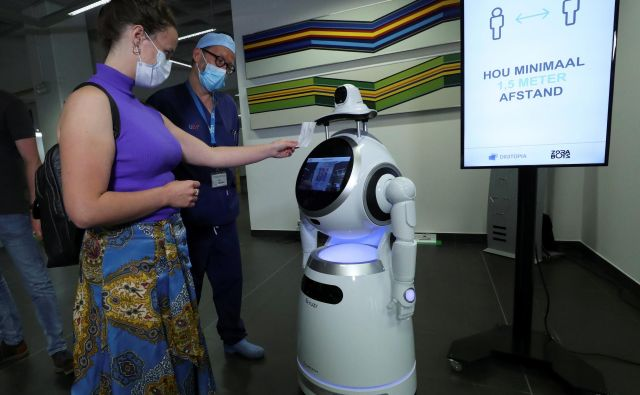 Kratkoročni cilj partnerstva za umetno inteligenco je ugotoviti, kako AI lahko pomaga pri odzivanju na covid-19. V univerzitetni bolnišnici v Antwerpnu roboti merijo telesno temperaturo obiskovalcev ter preverjajo, ali imajo ustrezno nameščene zaščitne maske. FOTO: Yves Herman/Reuters