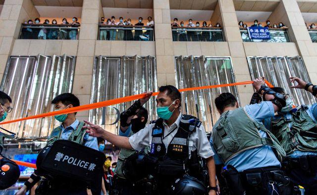 Policijsko preiskovanje trgovskega centra v Hongkongu, kjer ljudje čakajo na začetek današnjega protesta. FOTO: Anthony Wallace/AFP