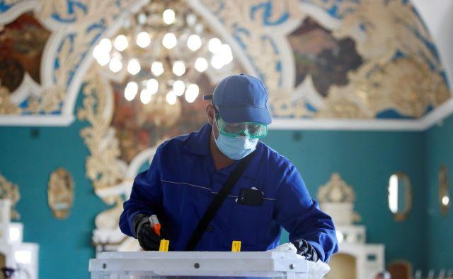 Del glasovanja v času pandemije je tudi razkuževanje volilnih skrinjic. FOTO: Maksim Šemetov/Reuters
