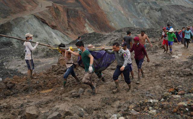 Reševalci iz blata odkopavajo trupla umrlih. FOTO: Zaw Moe Htet/AFP
