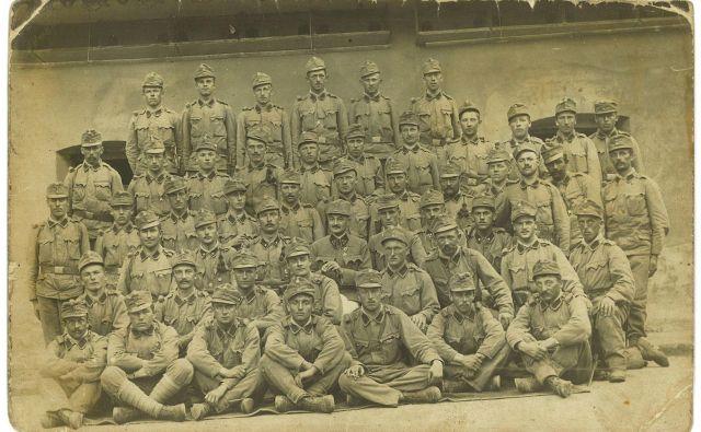 Dopisnica s skupino vojakov v Gleisdorfu pri Gradcu, ki jo je Lovro Kuhar poslal staršem 23. avgusta 1915. Lovro Kuhar stoji točno na sredini, tik nad sedečim stotnikom (verjetno Leo Dettela). Vir: Musilov inštitut v Celovcu