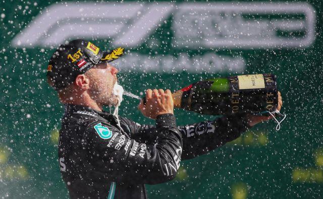Valtteri Bottas si je takole po včerajšnji zmagi v Spielbergu privoščil zasluženi požirek zmagovitega šampanjca. FOTO: Mark Thompson/AFP
