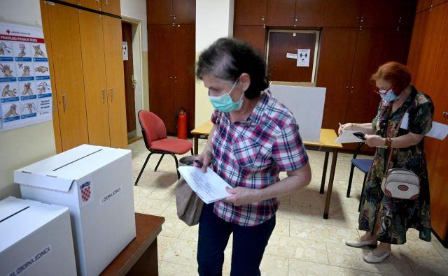 Parlamentarnih volitev na Hrvaškem se je danes do 16.30 udeležilo 34,04 odstotka volivcev, je sporočila hrvaška državna volilna komisija na svoji spletni strani. FOTO: Denis Lovrovic/AFP