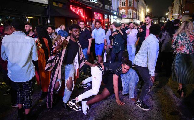 V Londonu so po daljšem času lokali odprli vrata, ljudje pa so se obnašali, kot da nevarnosti virusa ni več.Pubi in restavracije so bili večinoma polni, saj so si ljudje po več tednih zaželeli druženja.Socialna distanca oziroma dovolj velika razdalja med ljudmi, ki je ključna za preprečevanje širjenja novega koronavirusa, je pri pijanih ljudeh nemogoča, pravi angleška policija. FOTO: Justin Tallis/AFP