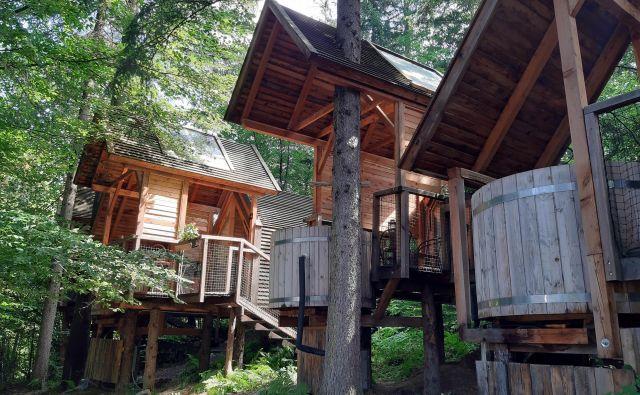 Kakor gobe so med drevesi posejane lesene hiške s svojimi malimi terasami. FOTO: Mitja Felc/Delo
