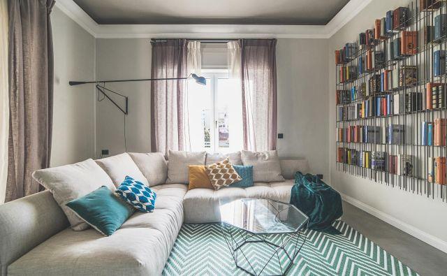 Osrednji bivalni prostor zaznamujeta knjižna omara iz kovinskih palic in preproga z geometrijskim vzorcem. Foto arhiv biroja Modo Architettura + Design