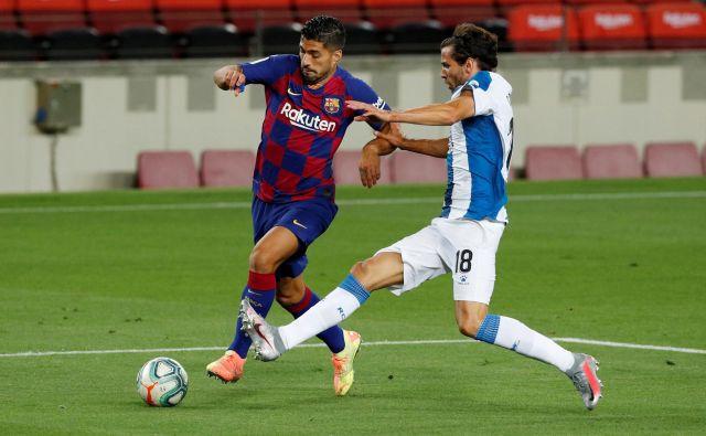 Barcelonin adut Luis Suarez in Espanyolov nogometaš Leandro Cabrera med katalonskim derbijem. FOTO: Albert Gea/Reuters