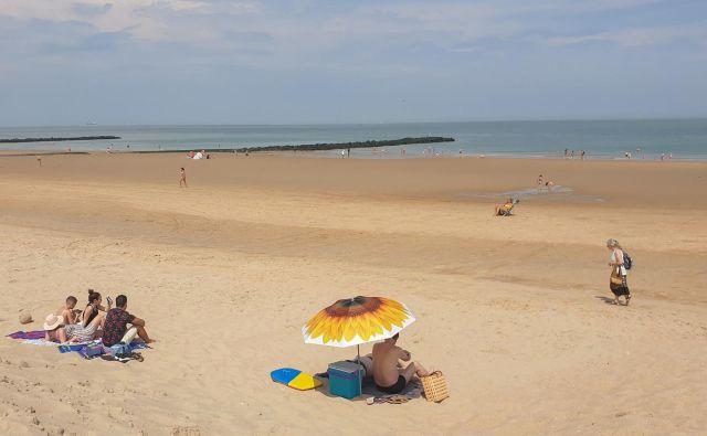 Redki kopalci na plaži v prestižnem belgijskem letoviškem kraju Knokke-Heist konec junija. FOTO: Clement Rossignol/Reuters