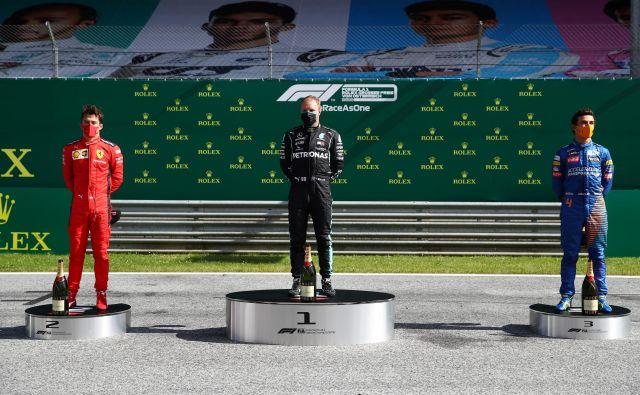Najboljši trije dirkači na uvodni letošnji dirki v formuli 1, finski zmagovalec Valtteri Bottas, drugouvrščeni Monačan Charles Leclerc (levo) in tretjeuvrščeni Lando Norris (desno), so se z maskami na obrazu povzpeli tudi na stopnice zmagovalnega odra. FOTO: Mark Thompson/Reuters