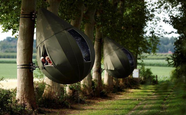 Gostje sedijo v šotoru v obliki solze, ki visi z drevesa. Nanavadni šotor je ustvaril nizozemski umetnik Dre Wapenaar in ponuja turistom nastanitev na belgijskem podeželju, blizu Borgloona. FOTO: Francois Lenoir/Reuters