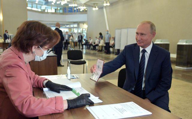 Vladimir Putin na volišču v Moskvi kaže svoj potni list. FOTO: Aleksej Družinin/AFP