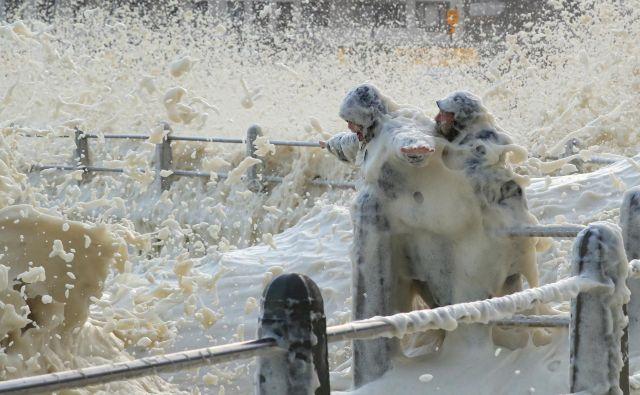 V Cape Townu se par podprt z ograjo nastavlja visokim valovom, ki udarjajo v valobran, saj se glavnem mestu Južnoafriške republike približuje hladna fronta. FOTO: Mike Hutchings/Reuters