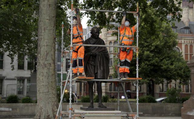 Potem ko so v Amsterdamu kip Gandhija premazali z barvo in popisali z grafiti, so oblasti v Londonu kip indijskega politika in aktivista iz previdnosti zaščitile. Foto Matt Dunham/AP