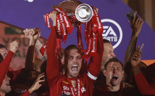 Jordan Henderson je pred dnevi visoko dvignil šampionski pokal v angleškem prvenstvu. FOTO: Phil Noble/Reuters