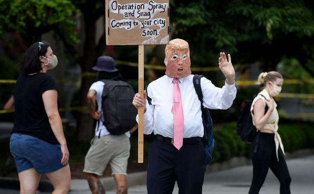 Protestnik v prestolnici Washington z masko predsednika Trumpa. Foto Olivier Douliery Afp