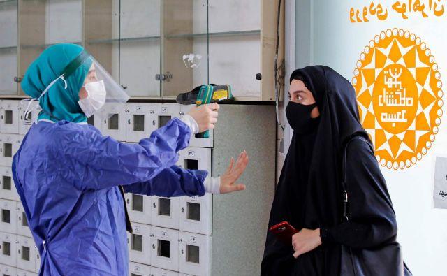 Merjenje temperature pred vstopom v eno od mošej v Teheranu. FOTO: Str/AFP
