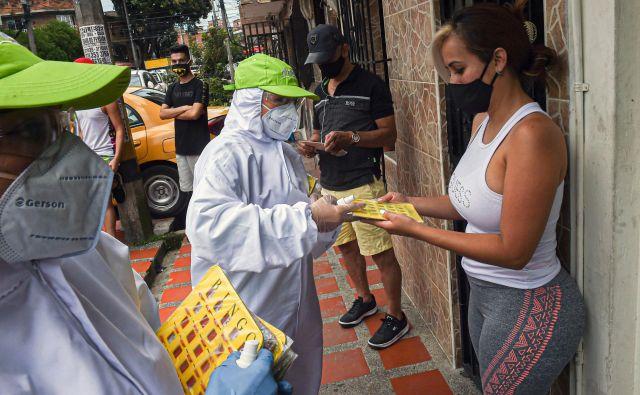 V kolumbijskem Medellinu ljudi motivirajo za ostajanje doma z igro Bingo. Na fotografiji razdeljevanje kartic. FOTO:Joaquin Sarmiento/AFP