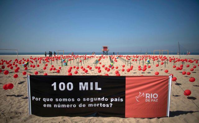 Plakat z napisom: 100.000. Zakaj smo druga država z največ smrtnimi primeri? Na slavni plaži Copacabana so izpustili na tisoče balonov, ki predstavljajo žrtve bolezni v Braziliji. FOTO:Mauro Pimentel/AFP