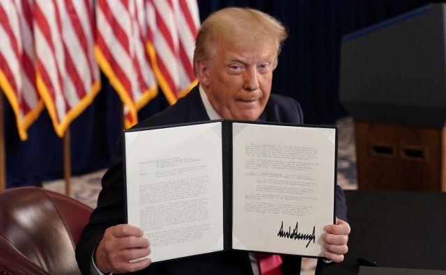 Donald Trump razkazuje svoj podpis pod izvršilnim zakonom.Foto Joshua Roberts Reuters