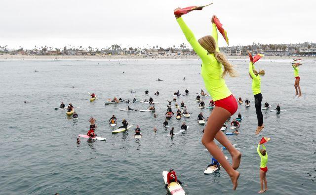 Mladi udeleženci programa za reševalce iz vode (San Diego Junior Lifeguard) skačejo s pomola na letnem obredu v Ocean Beachu v Kaliforniji. FOTO: Mike Blake/Reuters