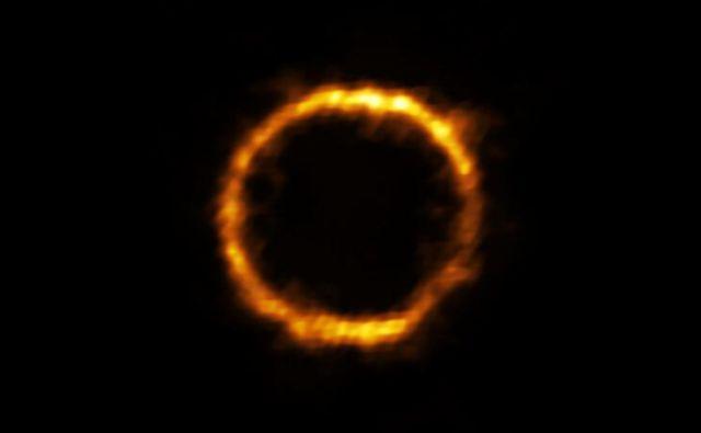 Z radijskim teleskopom Alma so opazovali zelo oddaljeno galaksijo, ki je bila s pomočjo gravitacijskega lečenja videti kot skoraj popoln obroč svetlobe. FOTO: ALMA (ESO/NAOJ/NRAO), Rizzo