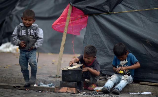 Deček gleda v posodo, ko se drugi igrajo v improviziranem taboru kolumbijskega avtohtonega plemena Embere v Bogoti. Žrtvam oboroženega konflikta in razseljenim staroselcem Kolumbije zdaj grozi nevidni sovražnik, novi koronavirus. Vlado prosijo za dostojna stanovanja za svojo skupnost in jamstva za vrnitev na njihova ozemlja. FOTO: Raul Arboleda/Afp