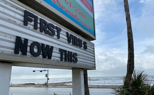 Znak, ki se sklicuje na koronavirusno bolezen in orkan Laura v kraju Galveston v Teksasu. FOTO: Julio Cesar Chavez/Reuters