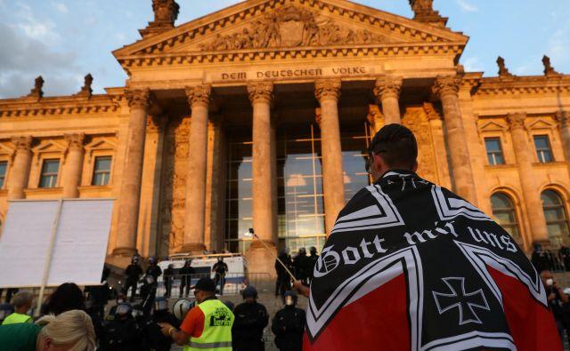 Nemški »Bog z nami« na zastavi. Protesta so se udeležile različne skupine, nekateri so na policiste metali kamenje in steklenice, za kar so oblasti okrivile desničarske skrajneže. FOTO: Christian Mang/Reuters
